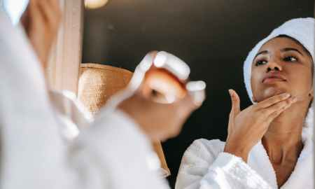 Black woman applying skin care product