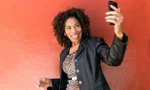 Elderly black woman holding phone up