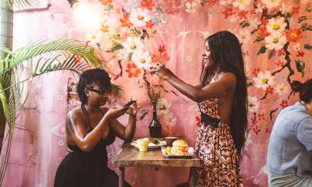 Black woman taking pictures of food at party