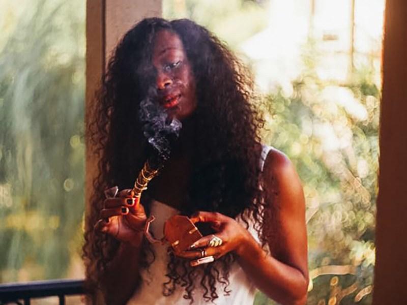 black woman burning sage herbal medicine