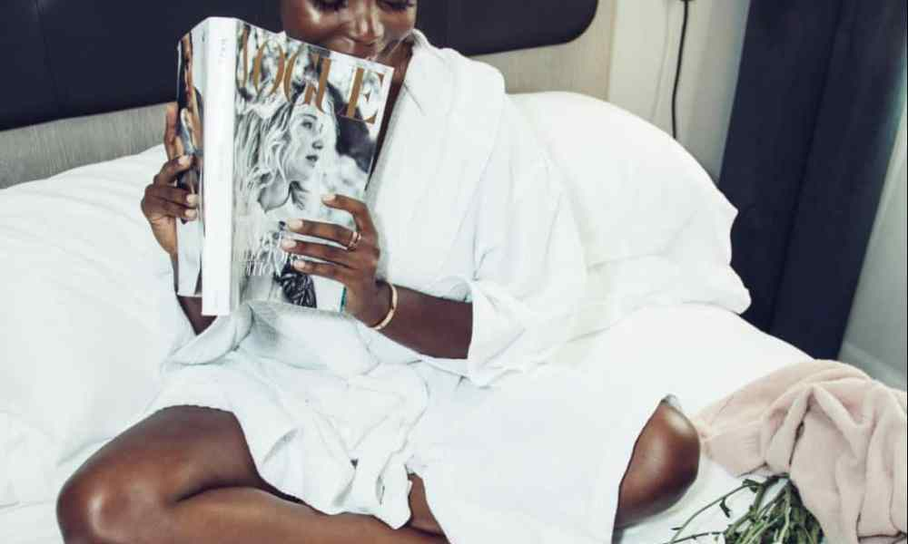 black woman sitting on bed wearing a robe and looking at skincare products