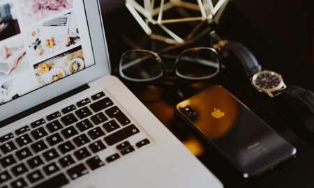 Elegant home office with golden accessories. MacBook, iPhone X, watch