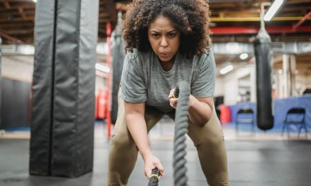 black woman working out with ropes at gym