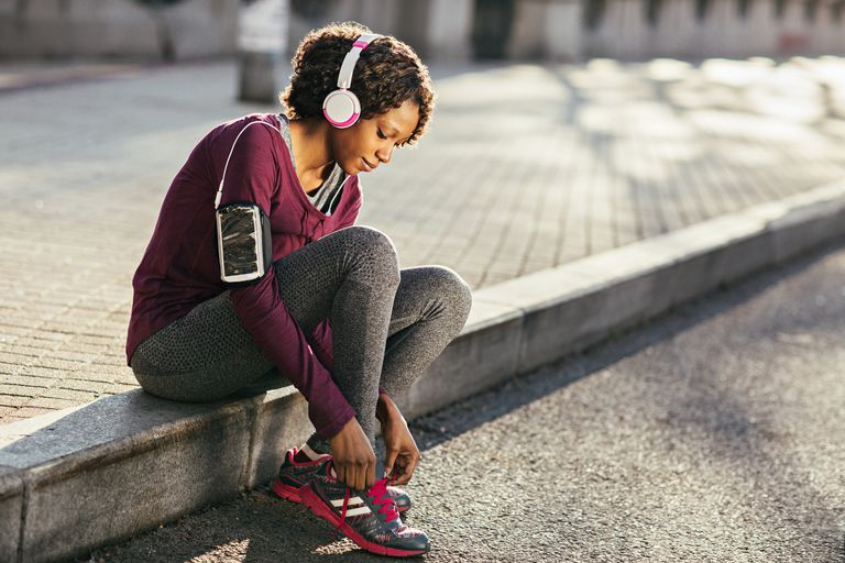 Young woman exercising and tying her shoelace