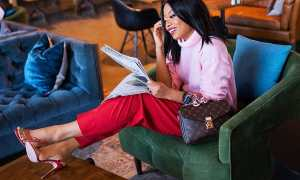 black woman reading newspaper in hotel lobby