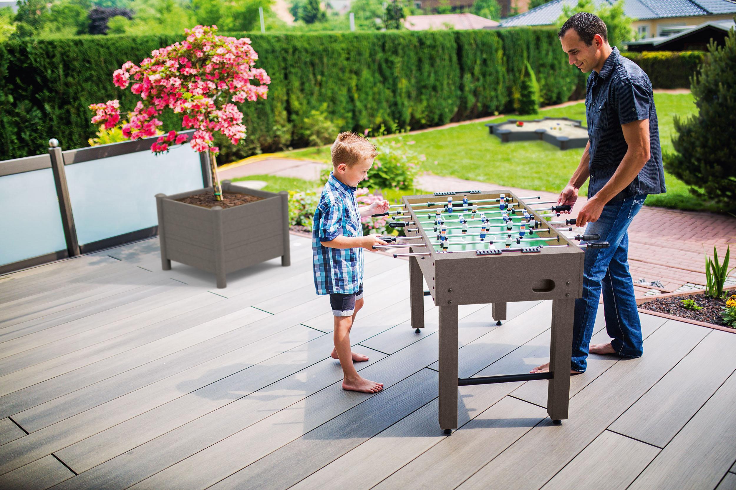Vater und Sohn kickern auf der Tarrasse - Nachhaltige Terrassengestaltung
