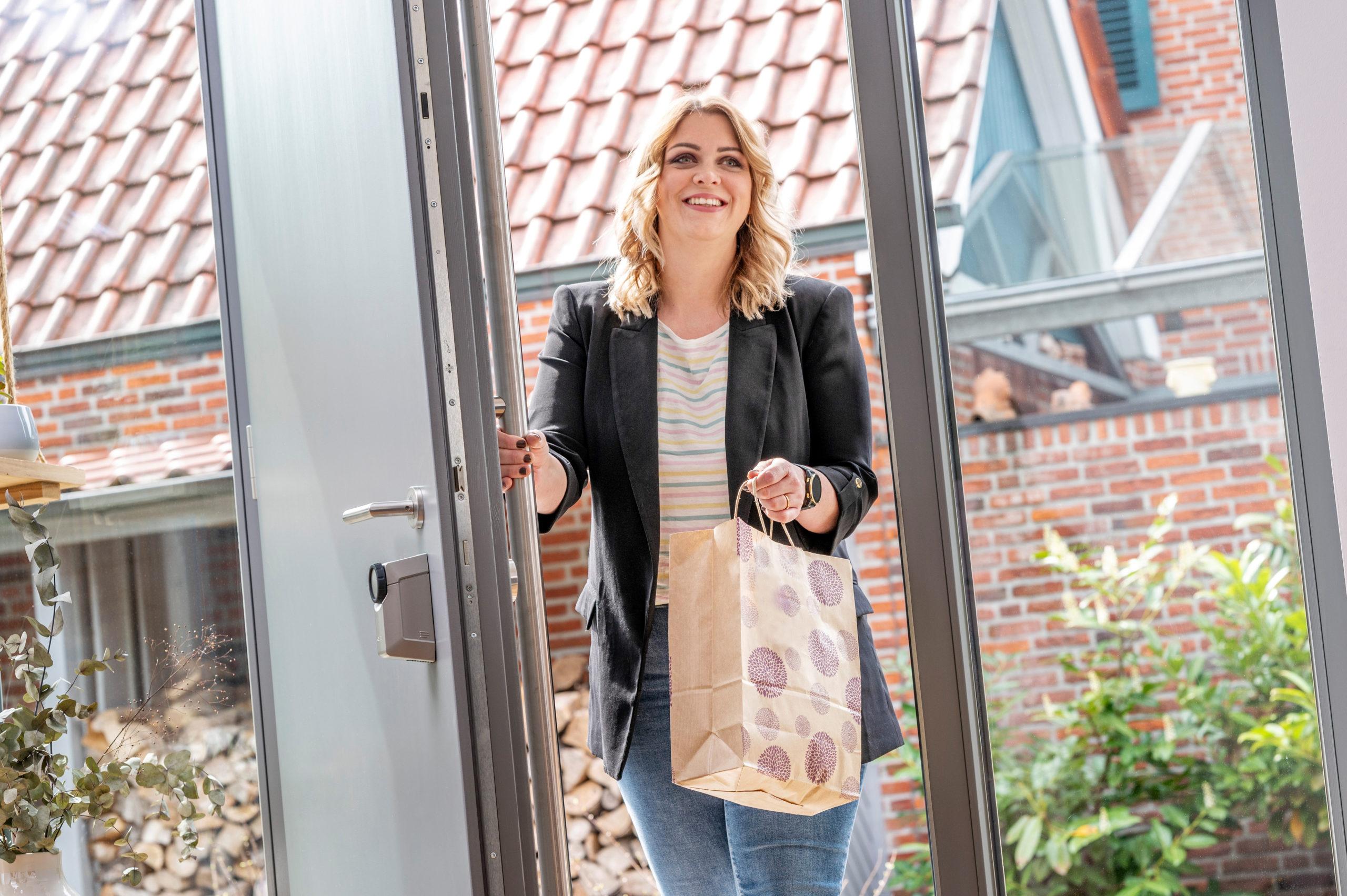 Frau nutzt Smartphone als Hausschlüssel