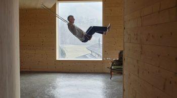 Mann schaukelt in einem Haus aus Holz