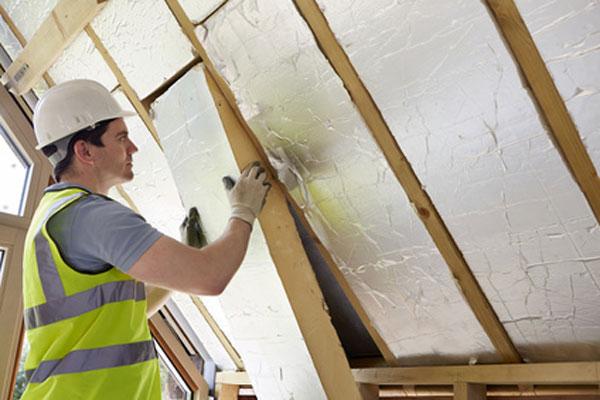 Ein Arbeiter isoliert ein Dach von innen mit Klemmfilzen