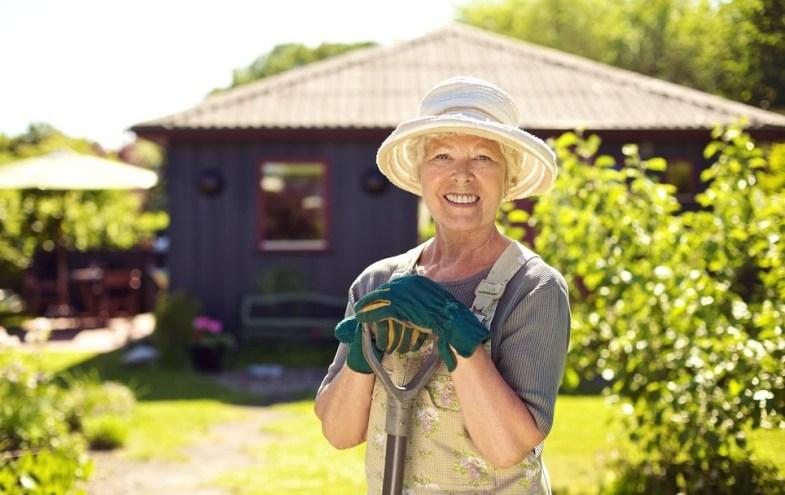 Ältere Dame vor Einfamilienhaus