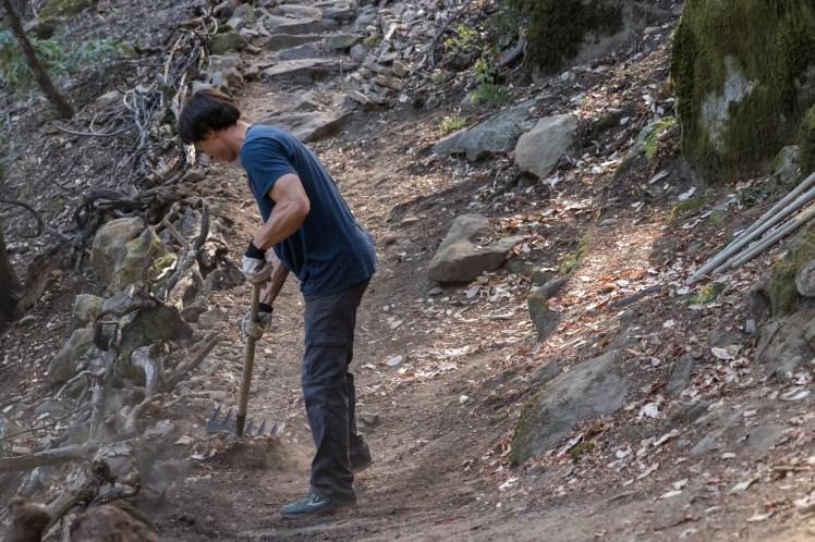 a volunteer regrading a trail