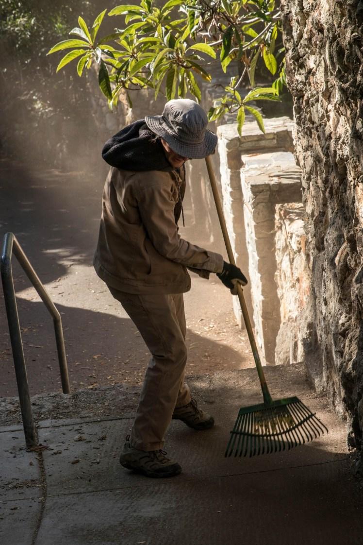 a volunteer rakes a stone stairway