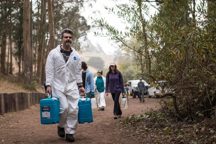 volunteers carrying jugs of water used to remove graffiti. The volunteer in focus wears a white Tyvek suit