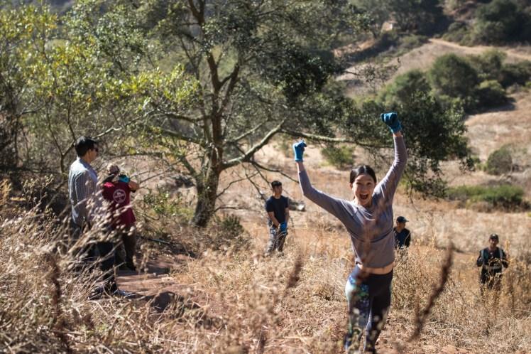 Volunteers working on trail repair. In the foreground, one volunteer excitedly cheers.