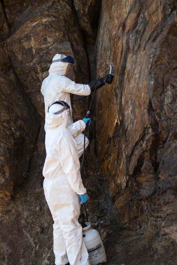 one volunteer brushes graffiti off a rock face while another sprays the area with water. Both wear white Tyvek suits and face shields.