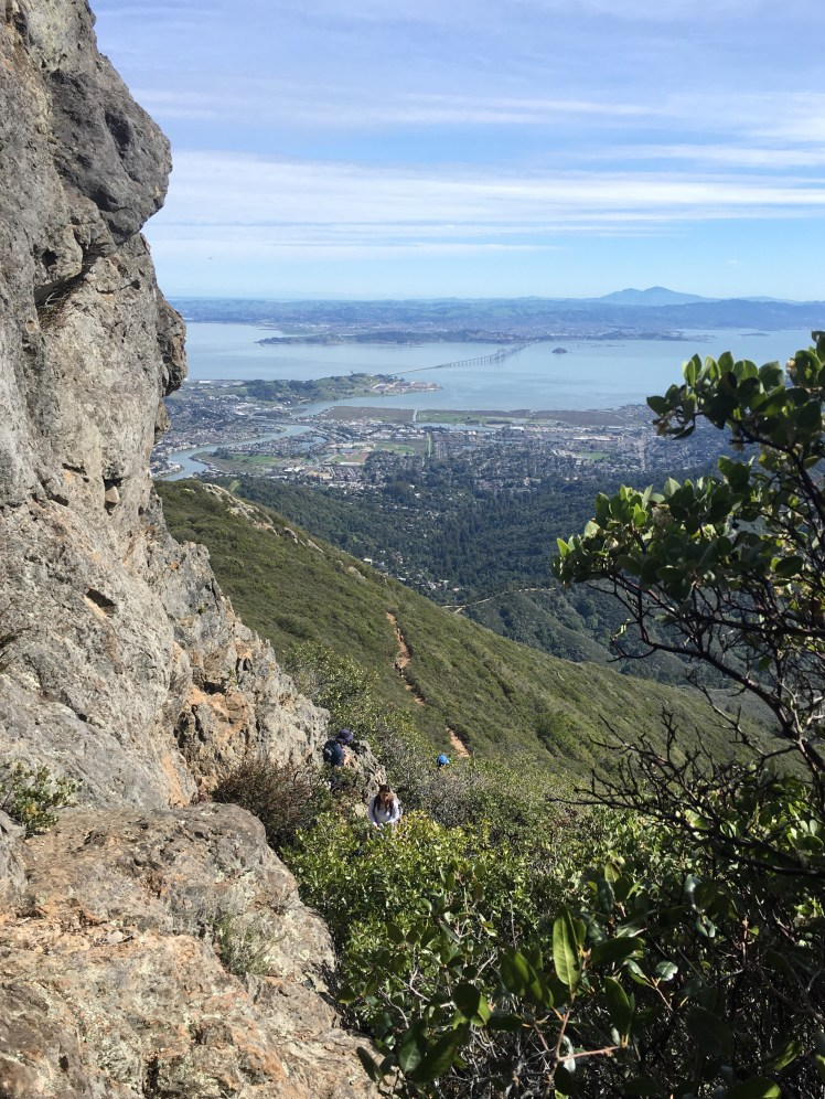 A view of San Pablo bay and Mt. Diablo in the distance as seen from a rock face at Mt. Saint Helena. There are three climbers on an approach path.