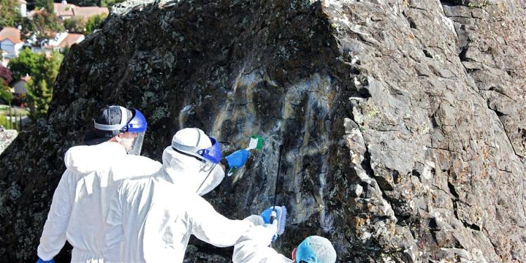 Volunteers in tyvek suits apply grafitti removal solution to a boulder covered in grafitti