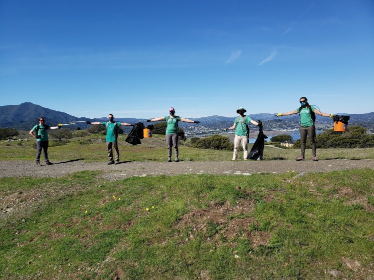 Masked BACC volunteer board members standing along a path atop Ring Mountain with their arms stretched out, demonstrating social distancing. They are holding implements for trash pickup: Buckets, bags, and pickers.
