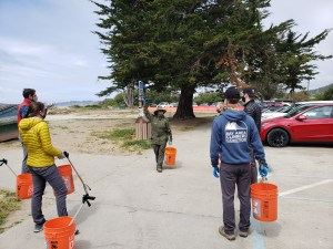 Volunteers stand in a parking lot with buckets and grabbers in their hand while listening to a park ranger.