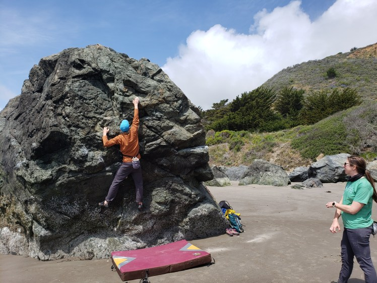 A person climbs up a boulder on the beach with a crash pad underneath them as another person looks on.