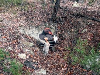 Karen peers down one of the barred mineshafts