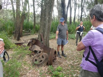 Paul pointing out an old piece of logging equipment with new member, Donna looking on