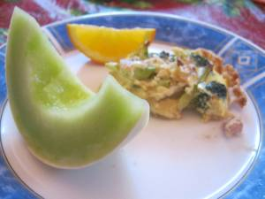 photo of quiche on plate with slice of honeydew melon