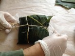 Wrapping the banh chung in a banana leaf and tying it to hold it together while cooking