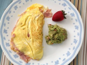 cheese and ham omelette with side of guacamole and a strawberry for garnish