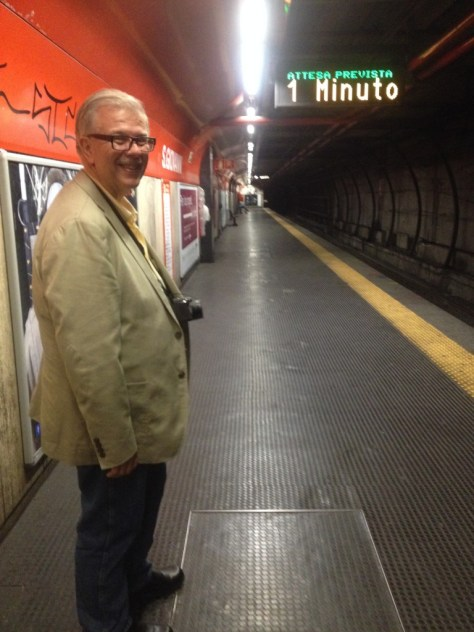 photo of my husband smiling with sign alerting us to next train in one minute in Italian