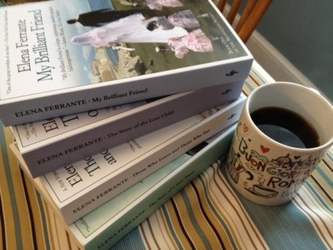 stack of four books by Elena Ferrante and coffee in a mug