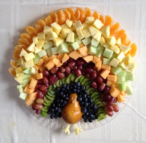 turkey made out of cut-up fruit with a half pear as the body