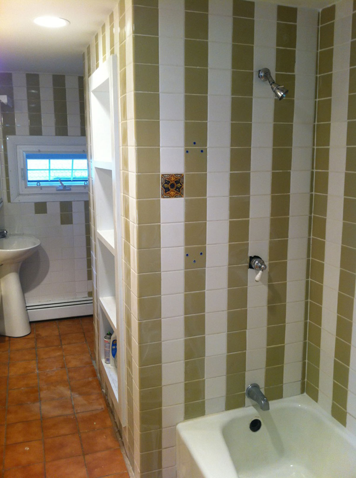 Floor to ceiling green and white striped tile in the bathroom before refinishing