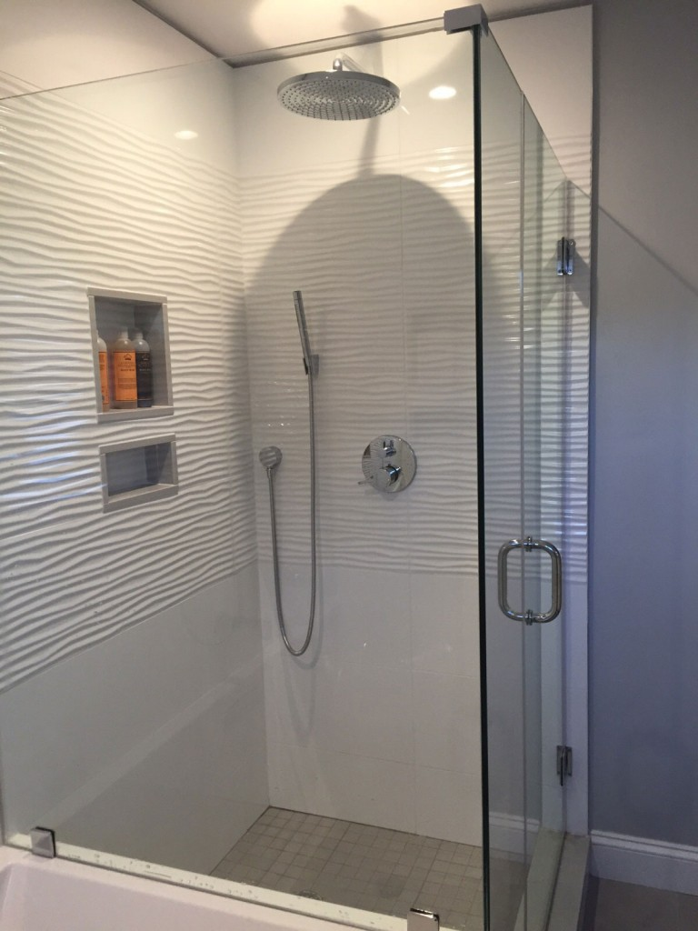 Walk-in glass-enclosed shower with floor to ceiling wavy white tile - Bay State Refinishing