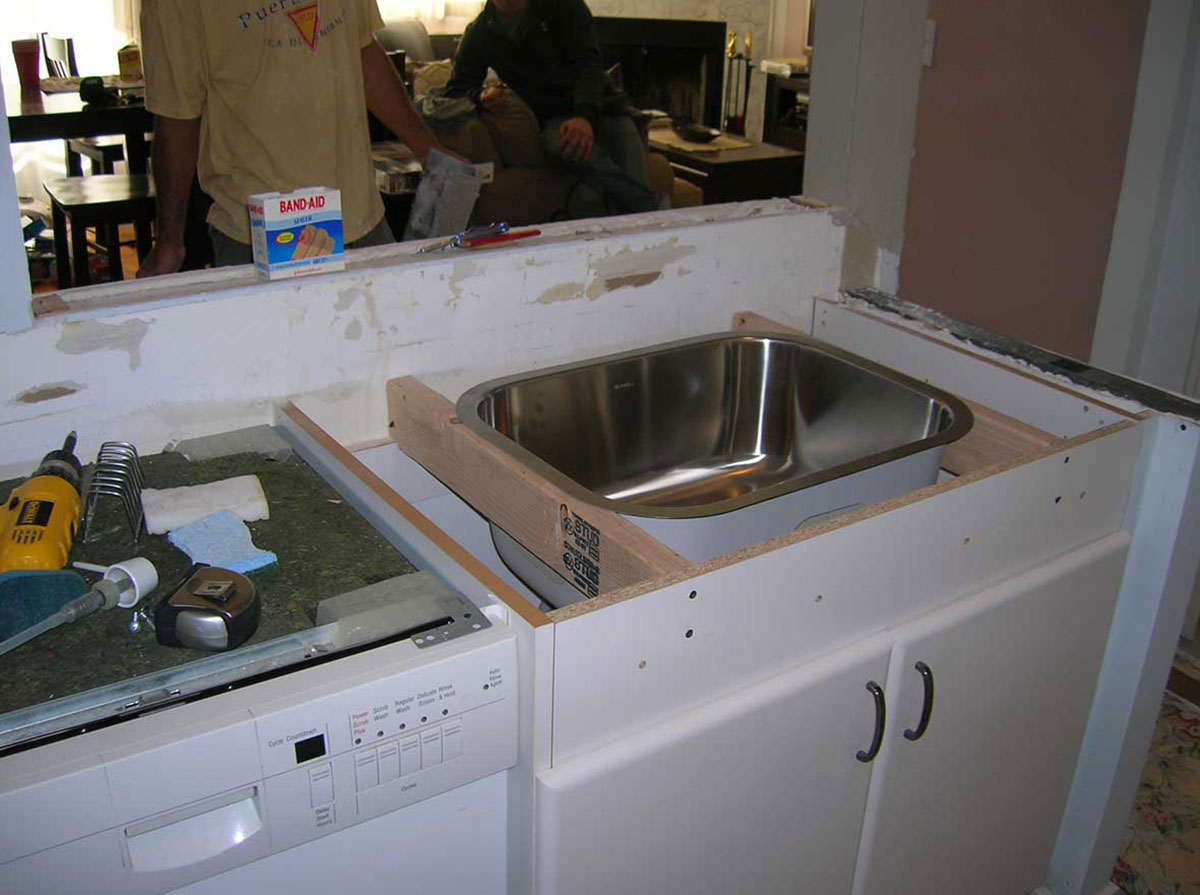 Stainless steel kitchen sink being fitted during kitchen remodel