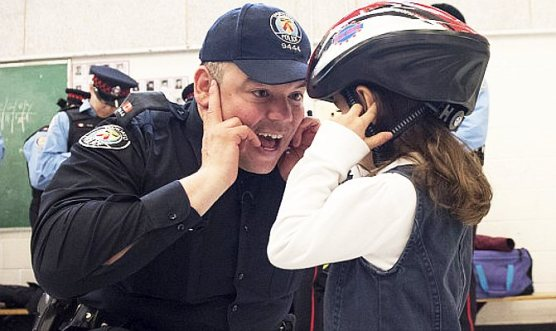 Kindergartener Rosalia gets advice from Constable Peter De Quintal on fitting her helmet