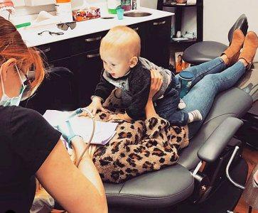 Baby comforts mom at dentist