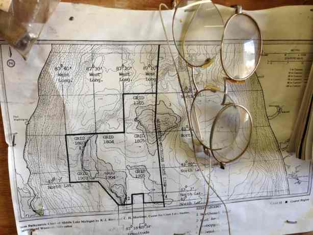 Wire rim spectacles hang over a bathymetric (depth) chart of Middle Lake Michigan on the wall of Alvin Anderson's net shed. —photo Katherine Keller