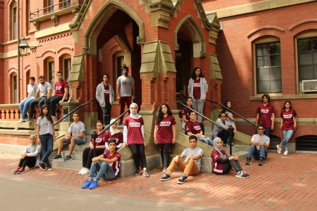The students posing in front of Harvard University.