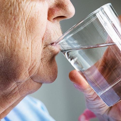 קשיש שותה מים למניעת מחלות בחורף