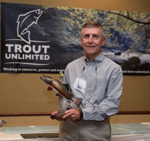 Dick Geiger, chair of the Tennessee Council of Trout Unlimited, shows off the brook trout carving he has just been presented during Trout Unlimited's annual meeting in Scranton, Pa. The carving signifies the council's recognition as the 2015 State Council of Excellence, one of the national organization's annual National Conservation Awards.