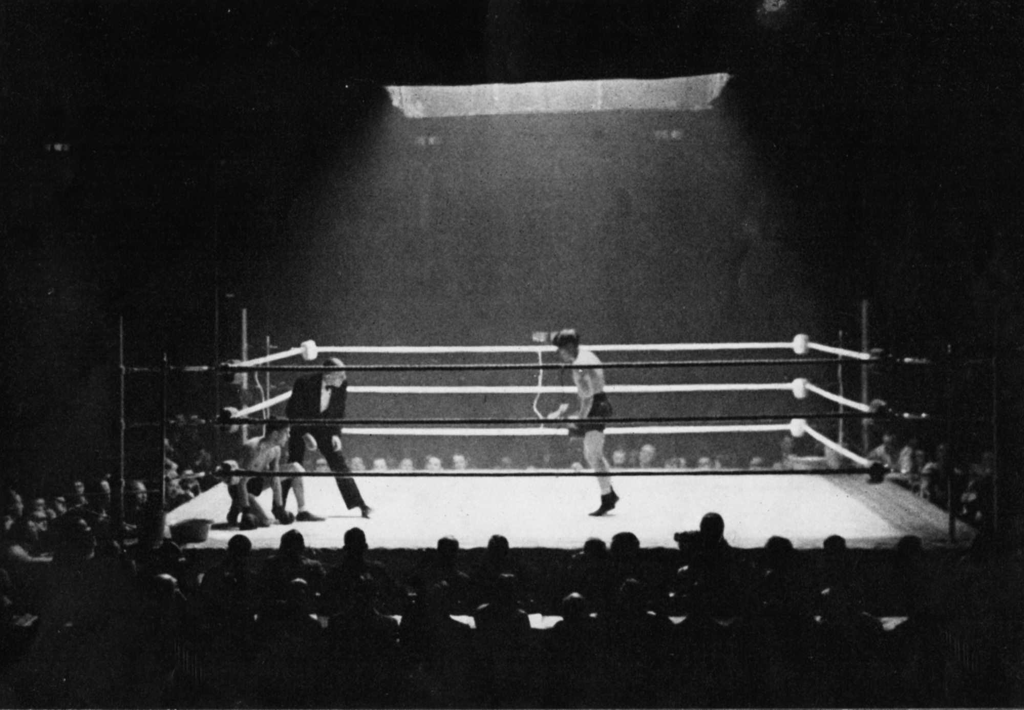 A boxing ring, dramatically lit from above