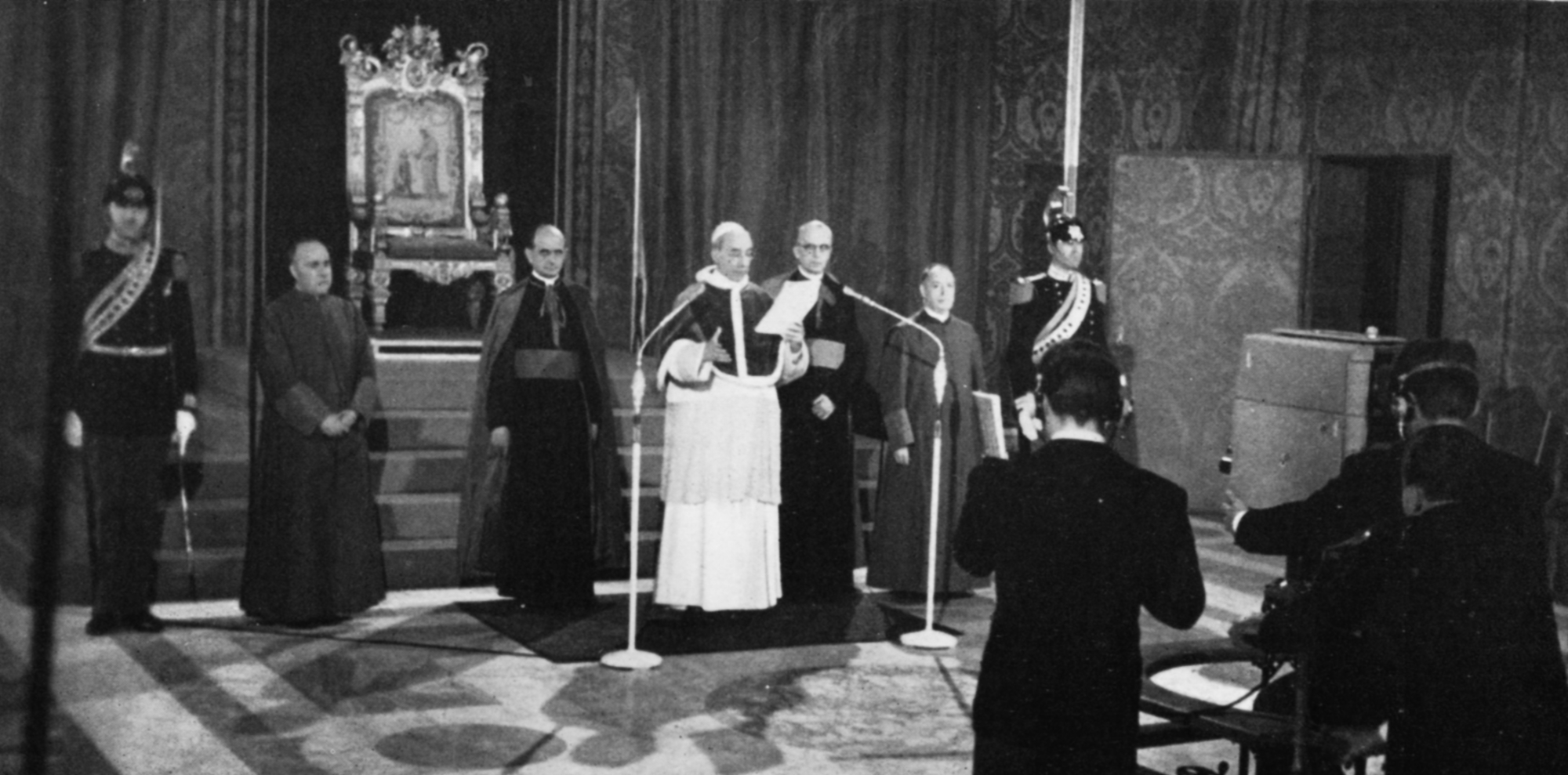 Pope Pius XII reads from a script with two microphones and a camera in front of him