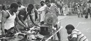 Young Black kids gathered around DJ decks at a block party