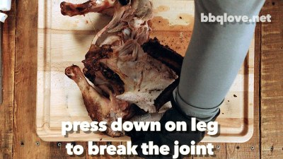 Press down on the turkey legs to break the joint. No need for a knife. Top down view. Turkey on a wood cutting board