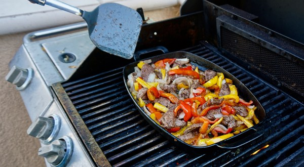 Fajita beef strips with chopped bell pepper on top and in pan on grill