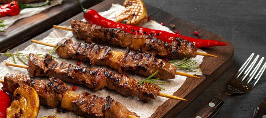 Grilled meat chunks on skewers laying on top of wooden board
