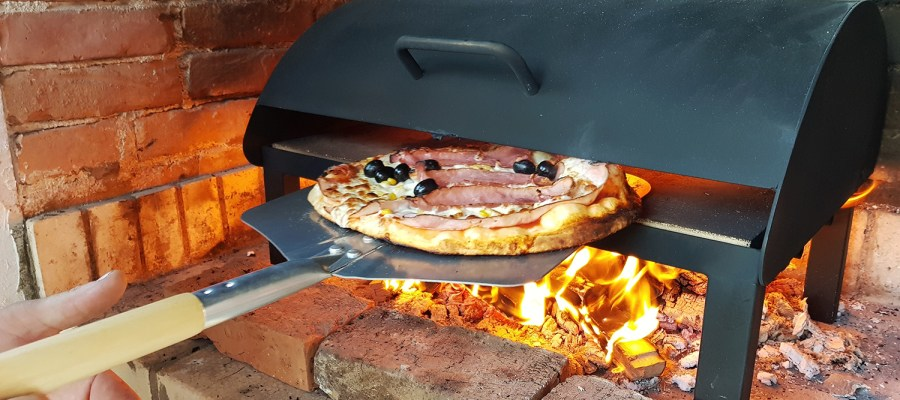 Pizza with bacon and olives being placed in outdoor pizza oven