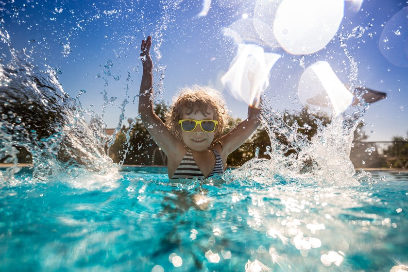 Happy child playing and splashing water in swimming pool
