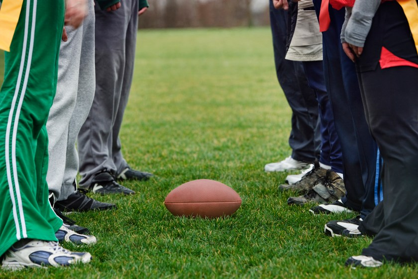 Image of friends feet who are lined up on both sides with a football on the grass between them